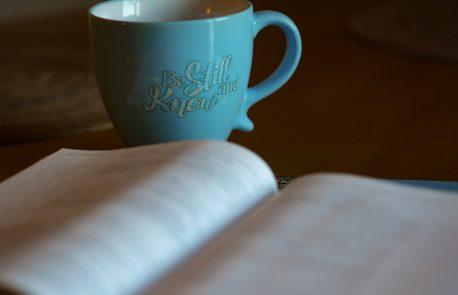 Bible open with coffee mug
