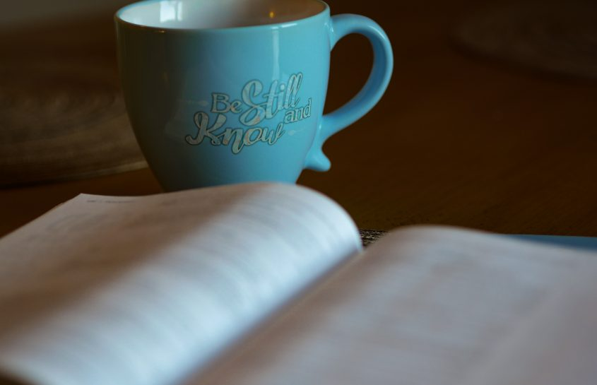 Bible open with coffee mug