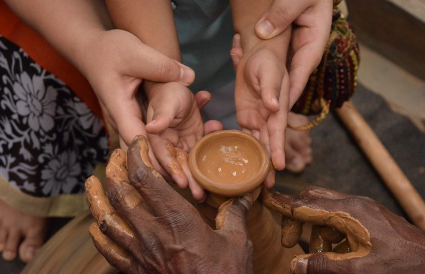 Woman and child hands shaping clay
